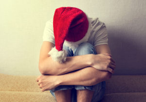 sad man in Santa Hat on the Couch, veteran PTSD and holidays