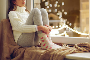 PTSD, sadness and people concept - sad beautiful girl in sweater sitting on sill at home window over christmas lights background