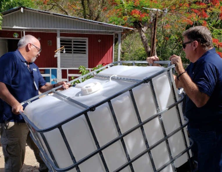 Water cisterns are delivered to a Puerto Rico community devestated by Hurricane Maria