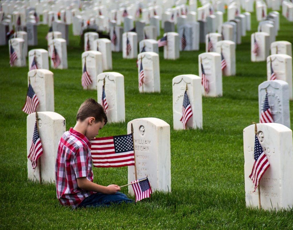 boy visiting Veteran tombstones