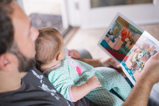 man reading to baby